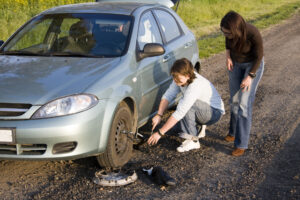 Two females changing a flat tire on the side of the road