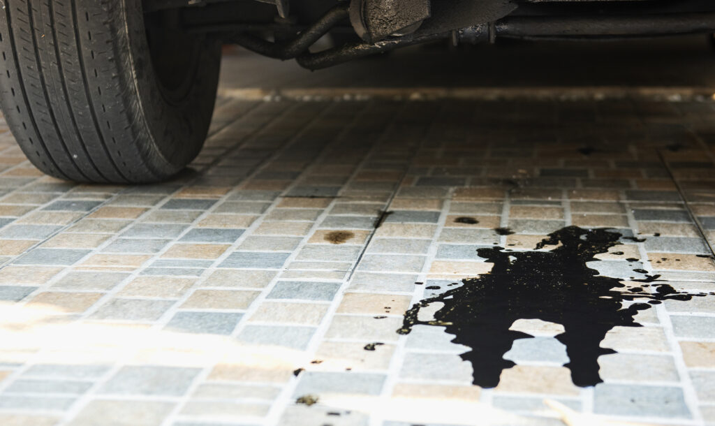 Oil leak from the car's engine on the parking lot. Car inspection and maintenance service