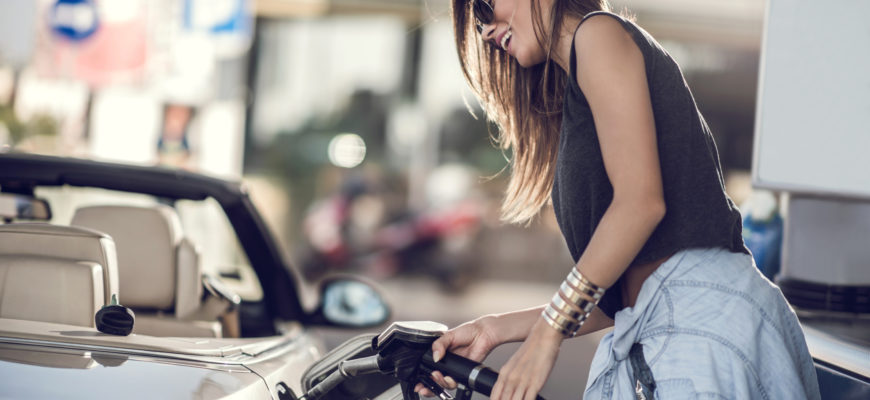 Woman refueling the gas tank at fuel pump.