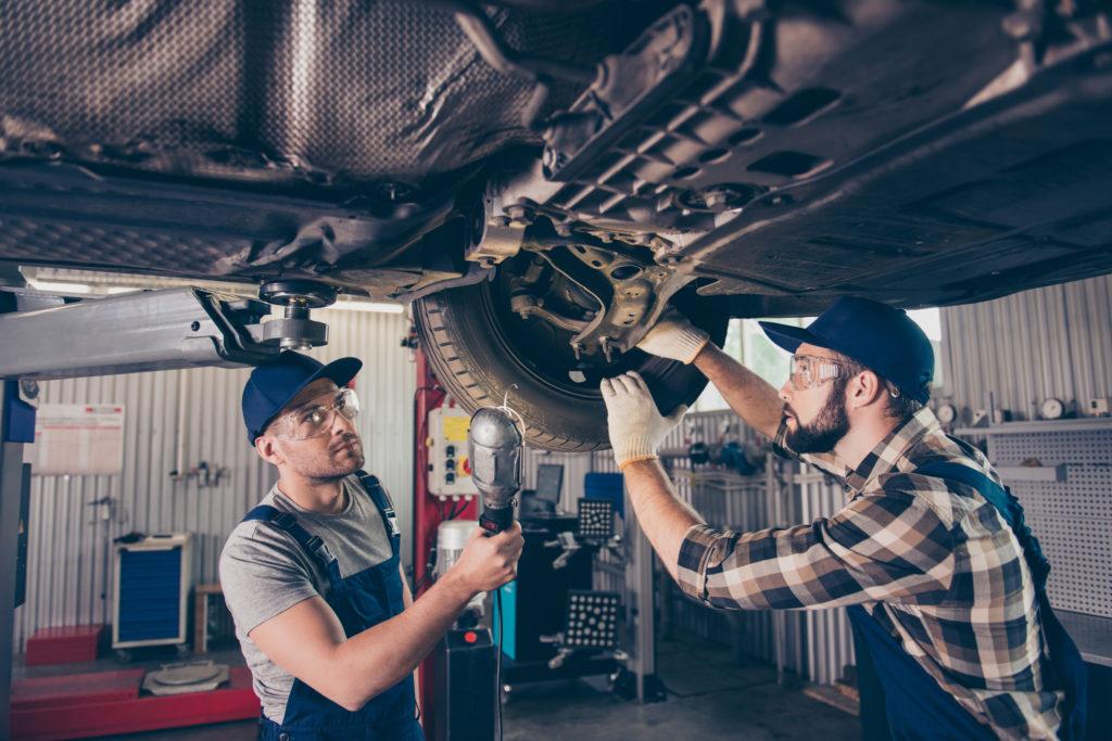 Auto mechanics working on car