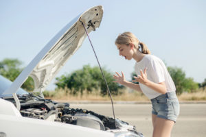 Young woman having a shock when her car broke down